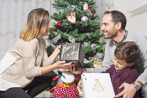 Happy family giving christmas gifts