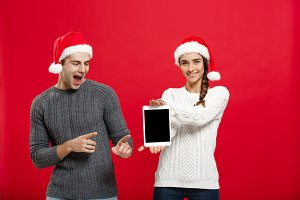 Christmas concept - Happy young couple in christmas sweaters surprising something in digital tablet.