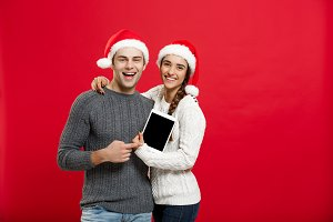 Christmas concept - Happy young couple in christmas sweaters holding digital tablet.