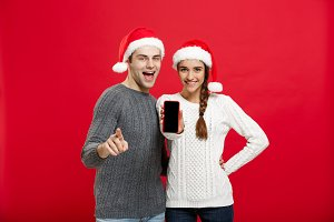 Christmas concept - Happy young couple in christmas sweaters pointing finger with mobile phone.
