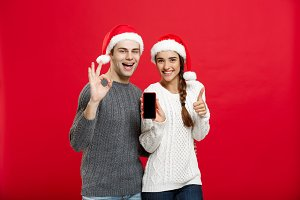 Christmas concept - Happy young couple in christmas sweaters showing ok gesture with mobile phone.