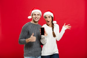 Christmas concept - Happy young couple in christmas sweaters showing thump up gesture with mobile phone.
