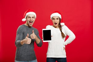 Christmas concept - Happy young couple in sweaters celebrating christmas with playing and dancing.