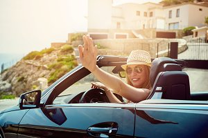 Young girl sitting in cabriolet and waving