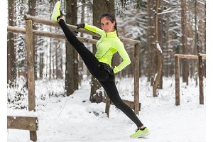 Fit woman athlete doing left leg split stretching exercises outdoors in woods. Female sports model exercising outdoor winter park