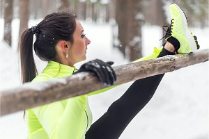 Fit woman athlete doing hamstring leg stretching exercises outdoors in woods. Female sports model exercising outdoor winter park.