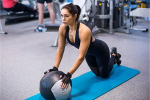 Fit woman exercising with medicine ball workout out arms Exercise training triceps and biceps doing push ups