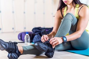 Fit sporty young woman tying shoelaces at gym.