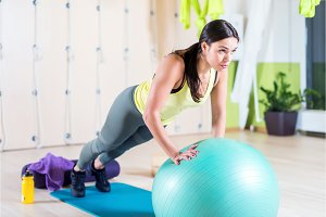 Fit woman doing push ups with medicine ball workout out arms Exercise training triceps and pectorals muscles