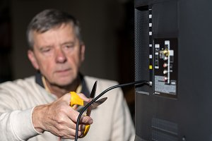 Senior man cutting the cord on his cable TV package