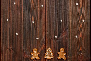 Christmas gingerbread man cakes around a Christmas tree on a brown wooden table. Copy space.