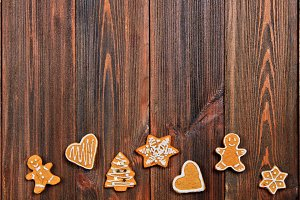 Christmas gingerbread cookies of different shapes on a brown wooden table. Copy space.