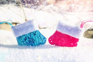 Blue and pink mittens on the snow in an embrace. Christmas toys. Male and female.
