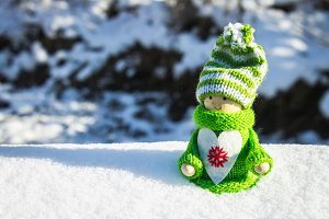 Toy wooden girl in Scandinavian style in knitted green clothes in the snow. Christmas toys.