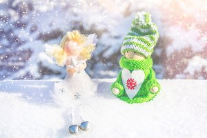 Toy wooden girl in Scandinavian style in knitted green clothes on the snow and angel. Christmas toys.