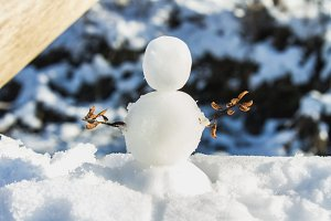 A small snowman with hands of twigs standing in the snow in the sun.