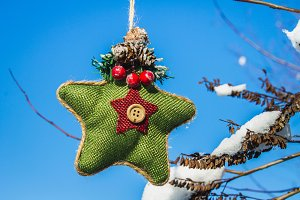 A green knitted star in Scandinavian style hangs on a branch with snow. Christmas toys.