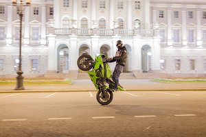 Male motorcyclist riding a wheelie at night on his sports bike on the green square in the centre of the old town