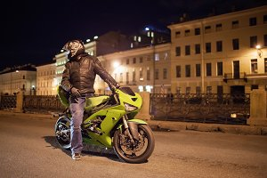 Motorcyclist in helmet on a green bike is on the road against the background of the night city