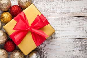 Golden gift box tied with a red ribbon isolated on white background. Top view. Copy space