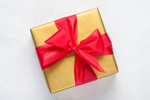 Golden gift box tied with a red ribbon isolated on white background. Top view