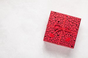 Single red gift box with hearts on white background. Top view with copy space