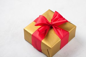 Golden gift box tied with a red ribbon isolated on white background