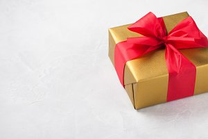 Golden gift box tied with a red ribbon isolated on white background. Copy space