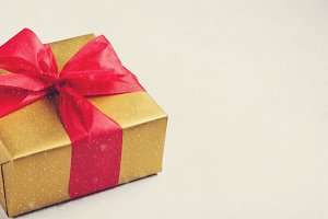 Golden gift box tied with a red ribbon isolated on white background. Copy space. vintage tones