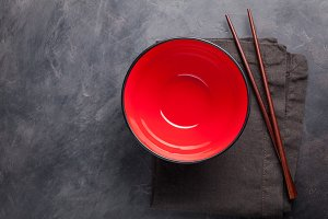 Empty red glass bowl of Chinese noodles and wooden sticks on dark concrete background. Top view with copy space. Flat lay