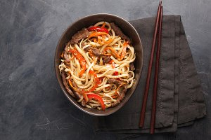 Close-up of noodles in a glass bowl with vegetables and beef in teriyaki sauce on a dark concrete background. Top view of Asian food, and wooden sticks. The concept of fast food