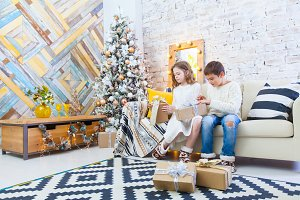 Two children a boy and a girl at a Christmas tree on a sofa with gifts. In light colors.