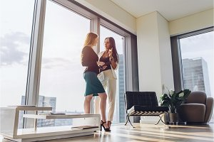 Two female business partners discussing plans standing in modern office at tower block