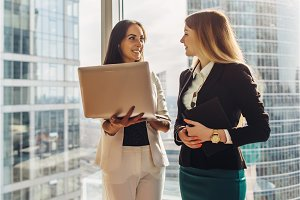 Smiling young women with laptop standing and talking in office