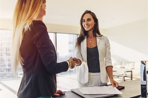 Female customer shaking hands with real estate agent agreeing to sign a contract standing in new modern studio apartment