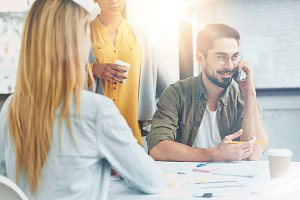 Young people work for common startup. Handsome male with beard in eyewear discuss general details with business partner, sits at work place. Group of creative workers collaborate. Flare effect