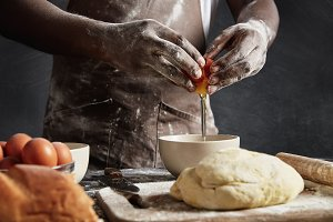 Man`s hands break egg in bowl as prepares pastry. Cropped shot of busy male cook bakes delicious cakes or white loaf, has dirty hands and uniform, stands near working table with ingredients.