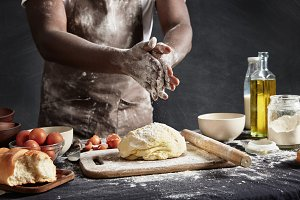 Cropped shot of busy African male cook kneads dough, prepares to show his culinary talents, poses near workplace with ingredients, isolated over black background. Cooking and people concept.