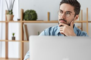 Serious pensive male businessman wears spectacles, works on laptop computer, thinks about future meeting, sits over office interior. Thoughtful bearded manager or freelancer generates new ideas