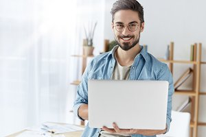 Handsome cheerful bearded young male copywriter types information for advertisment of website, wears stylish clothes and round spectacles, stands in coworking office, uses modern laptop for work