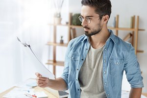 Serious bearded young male in stylish clothes reads seriously document, studies contract terms, goign to sign it, stands over cozy interior. Concentrated fashionable guy works with papers indoor