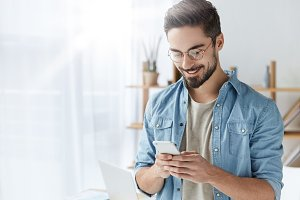 Glad fashionable young bearded guy wears stylish clothes and denim shirt, has trendy hairstyle, happy to exchange messages with friends, uses free internet connection on electronic modern