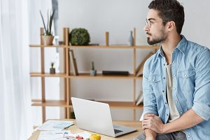 Thoughtful creative male designer tries to imagine new project, wears denim casual shirt, looks aside pensively, sits at table, uses laptop for work. People, occupation, lifestyle, technology concept