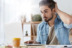 Experienced professional young bearded male enterpreneur ponders on idea for creation successful business, scratches head as looks in laptop computer, searches necessary information, works remotely