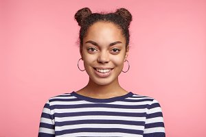Portrait of cheerful dark skinned female with two hair buns, dressed in casual striped sweater, glad recieve good news about including in staff or puting on list, expresses positive emotions