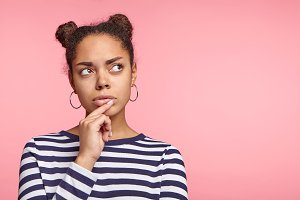 Mixed race female model looks pensively asise, tries to make decision, keeps finger on lips, poses agianst pink background with copy space for your promotional text. People and body language concept