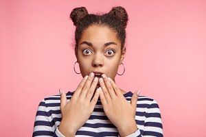 Stupefied shocked young female has two hair buns shows something dangereous or awful, stares at camera, covers mouth with hands, shocked to hear bad news isolated on pink background. Human expressions