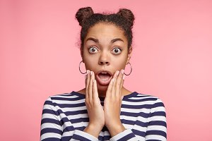 Portrait of shocked woman with dark skin and two hair knots, being surprised or astonished to see large discounrs at shop, isolated over pink background. Great disbeief and surprisment concept.