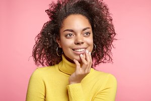 Curly pleasant looking mixed race female looks pensively aside, has dreamful expression, thinks about something pleasant, dreams of mutual love and perfect relationships. Facial expressions concept