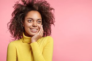 Horizontal portrait of positive dark skinned African American female model keeps hand on cheek, looks dreamfully aside, rejoices having holidays, poses against pink background with copy space